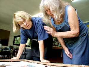 Cathy Naro and Maureen checking some of Cathy's prints